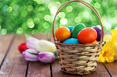 Basket with natural painted Easter eggs, surrounded by tulips and daffodils