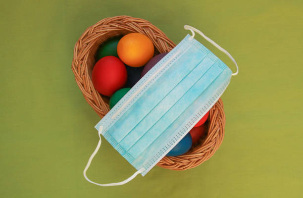Colored eggs in basket medical mask Easter 2020 stock photo