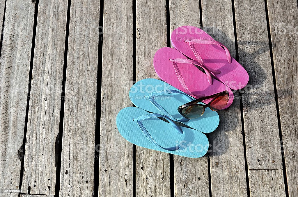 Colored flip flops and sunglasses on the wooden floor royalty-free stock photo