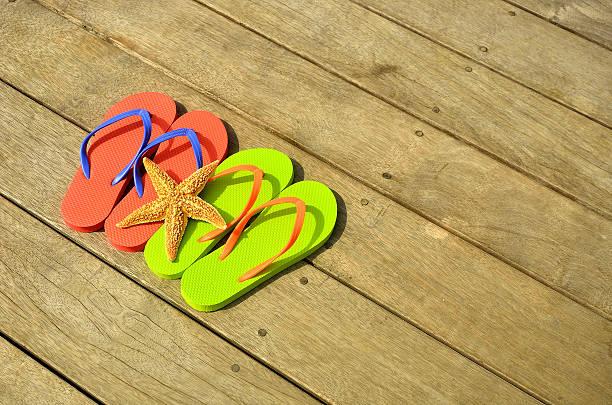 farbenfrohe flip-flops und seestern auf dem holzboden - flitterwochen flip flops stock-fotos und bilder