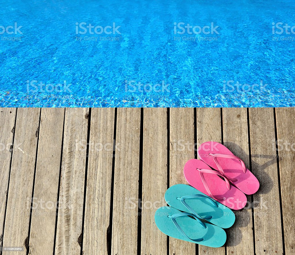 Colored flip-flops beside the swimming pool stock photo