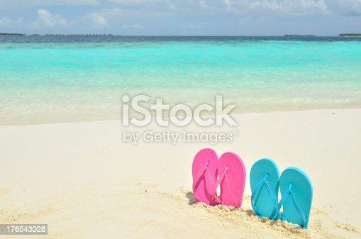 istock Colored flip-flops on the sandy beach 176543028