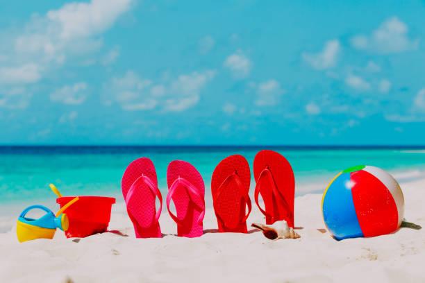 bunte flip-flops, spielzeug und tauchmaske am strand - flitterwochen flip flops stock-fotos und bilder