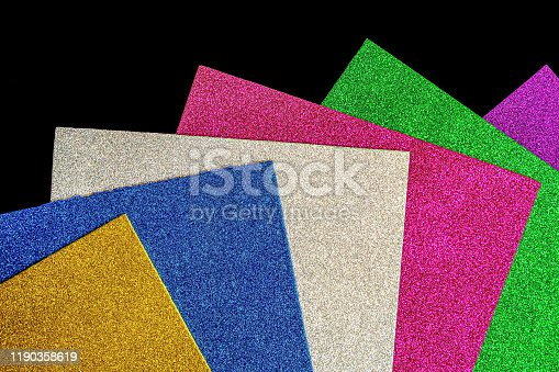 Colored foamiran sheets with sparkles on black background
