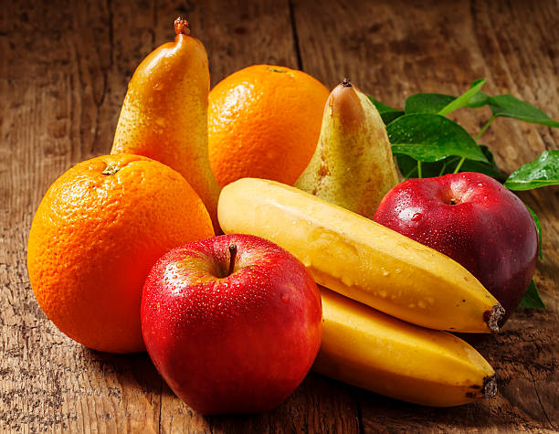 Colored fruits on wooden table stock photo