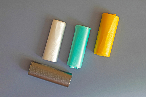 Four colored garbage bags roll on gray background