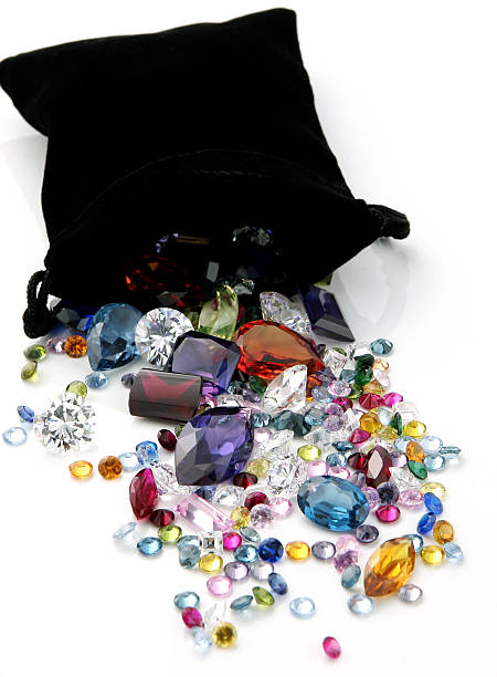Colored Gemstones Spilling out of Black Bag stock photo