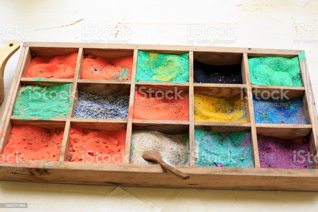 Colored gravel stones for tree art with wooden spoon in wooden bucket box stock photo