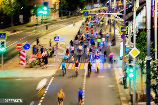 929609038istockphoto Colored group of bicyclists on city street. Parade of bicyclists, blur effect, unrecognizable faces. Abstract background. Sport, fitness, healthy lifestyle concept 1017778378