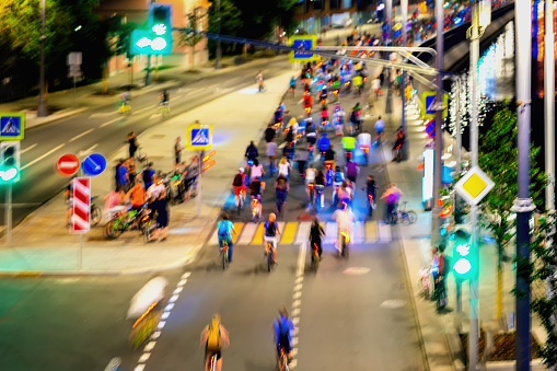 929609038 istock photo Colored group of bicyclists on city street. Parade of bicyclists, blur effect, unrecognizable faces. Abstract background. Sport, fitness, healthy lifestyle concept 1017778378