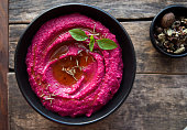 colored hummus, classic hummus, beet hummus, hummus on a dark rustic background. Top view, flat lay. Clean eating, dieting, vegetarian party food.