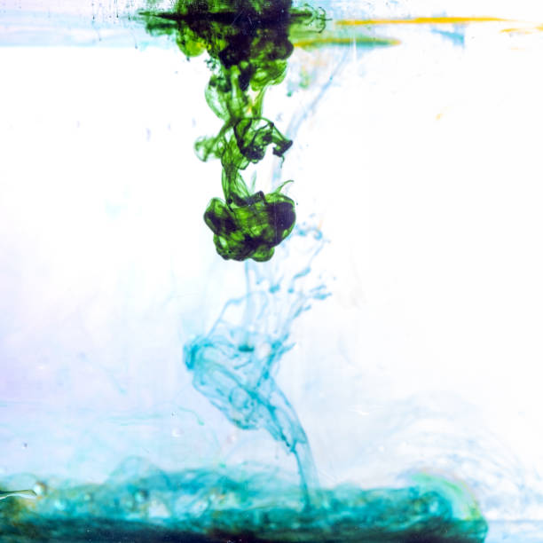 Colored ink cloud grows in water stock photo
