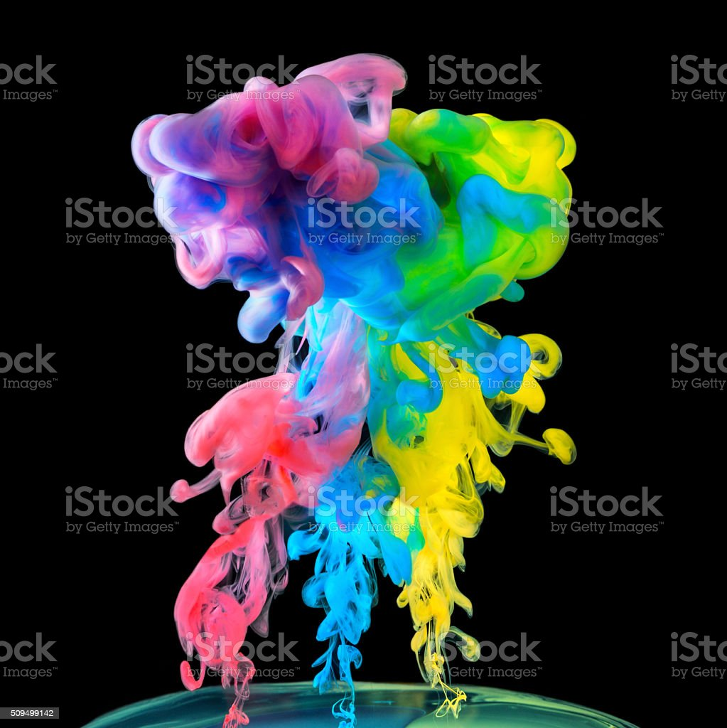 Colored inks in water on black background stock photo