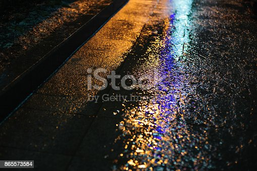 istock Colored light on wet asphalt in night city 865573584