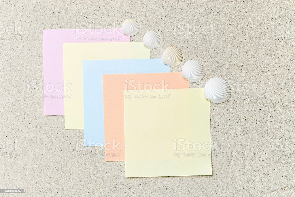 Colored notes with seashells on sand royalty-free stock photo