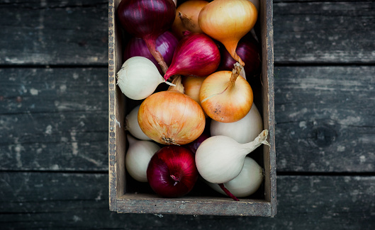 colored onion in a box on wood background.Top view