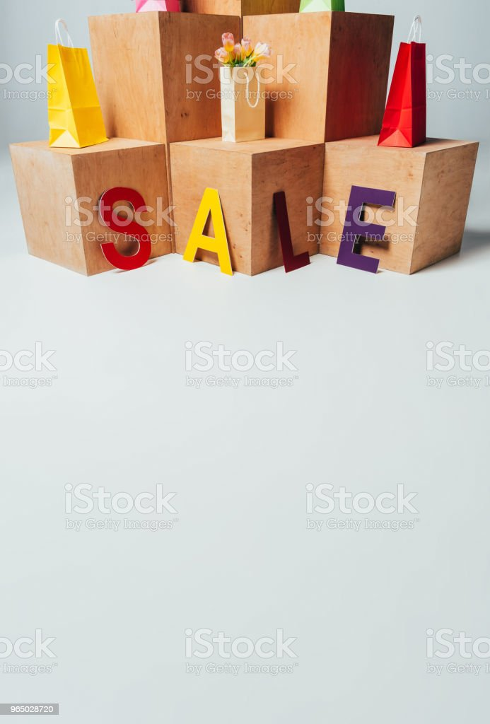 colored paper bags on wooden stands with sale sign, summer sale concept royalty-free stock photo