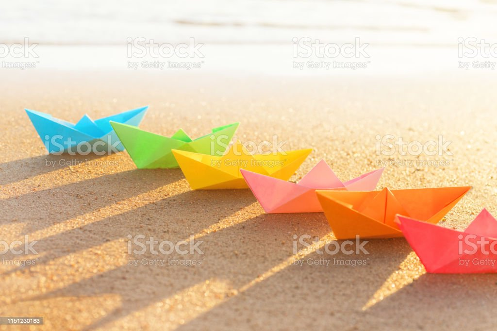 Colored paper boats row on sandy beach outdoors at sunset. Selective...
