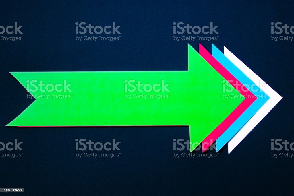 Colored paper right arrow on dark blue background. stock photo
