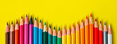 Colored pencil rainbow wave art school education in yellow background copy space