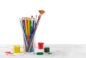 Colored pencils and brushes to draw in glass and watercolor paints