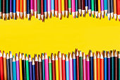 colored pencils lie next to each other in the form of a fence on a yellow background. Flat lay. Top view.
