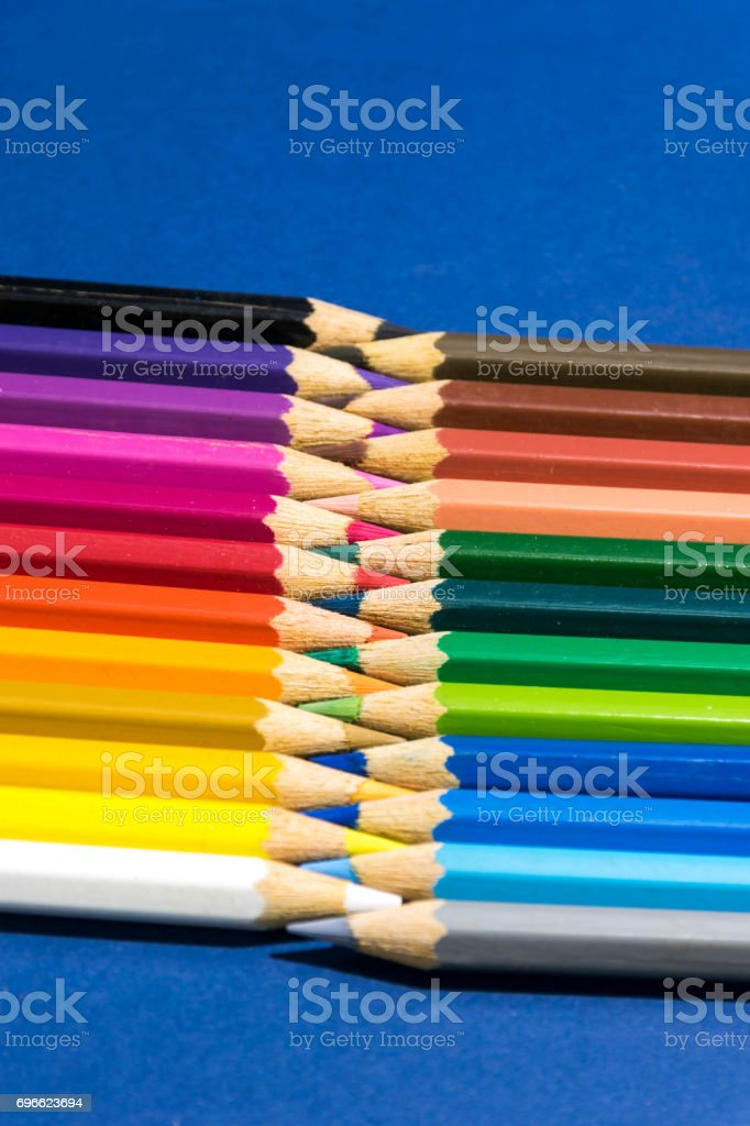Colored pencils on a blue background stock photo