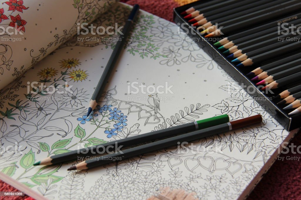 Colored pencils on an open coloring book stock photo