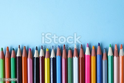 istock Colored pencils on blue background, copy space. Back to school concept. Flat lay, top view 1154294104