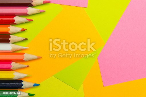 istock Colored pencils on the multi-colored paper background. Concept back to school. Geometric paper texture background. Template 1006189774