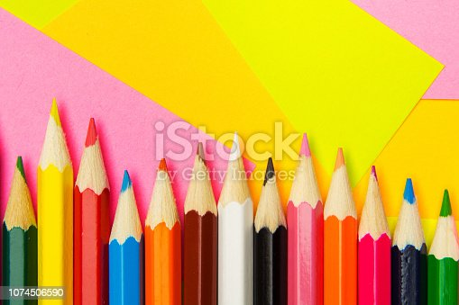 istock Colored pencils on the multi-colored paper background Concept back to school. Geometric paper texture background. Template 1074506590