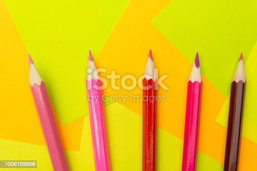 istock Colored pencils on the multi-colored paper background.Concept back to school. Geometric paper texture background. Template 1006189956
