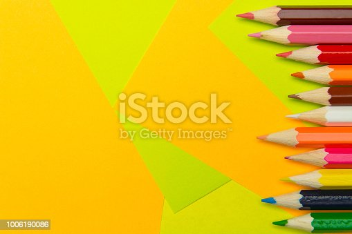 istock Colored pencils on the multi-colored paper background.Concept back to school. Geometric paper texture background. Template 1006190086