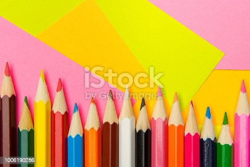 istock Colored pencils on the multi-colored paper background.Concept back to school. Geometric paper texture background. Template 1006190286
