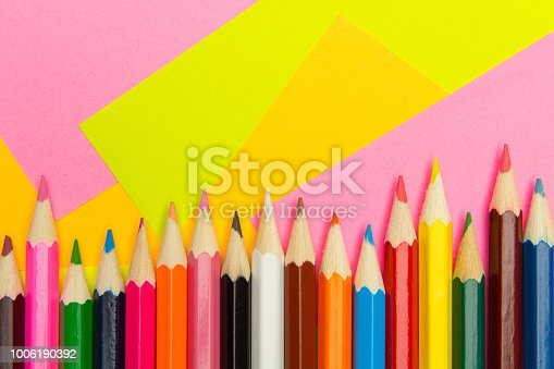 istock Colored pencils on the multi-colored paper background.Concept back to school. Geometric paper texture background. Template 1006190392