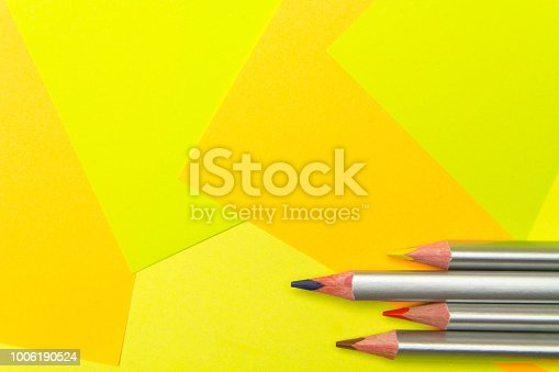 istock Colored pencils on the multi-colored paper background.Concept back to school. Geometric paper texture background. Template 1006190524
