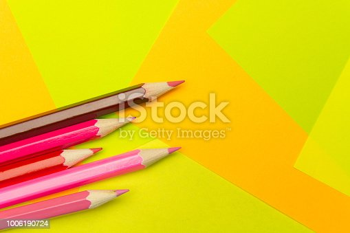 istock Colored pencils on the multi-colored paper background.Concept back to school. Geometric paper texture background. Template 1006190724