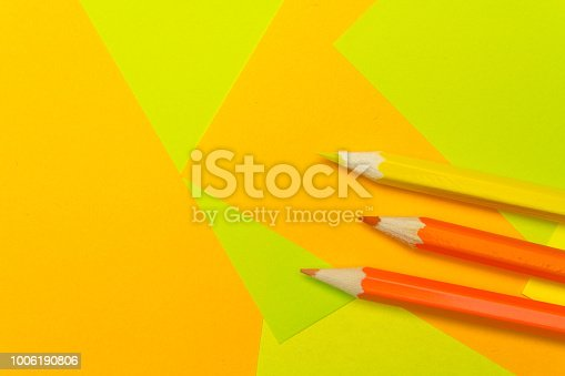 istock Colored pencils on the multi-colored paper background.Concept back to school. Geometric paper texture background. Template 1006190806