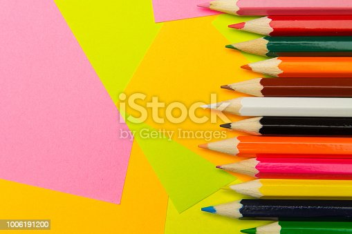 istock Colored pencils on the multi-colored paper background.Concept back to school. Geometric paper texture background. Template 1006191200