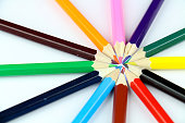 Set of colored pencils arranged in circle on white background.