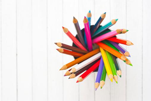 color pencils in tincan, wood table