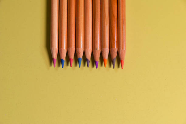 Colored pencils placed on a green surface - foto stock