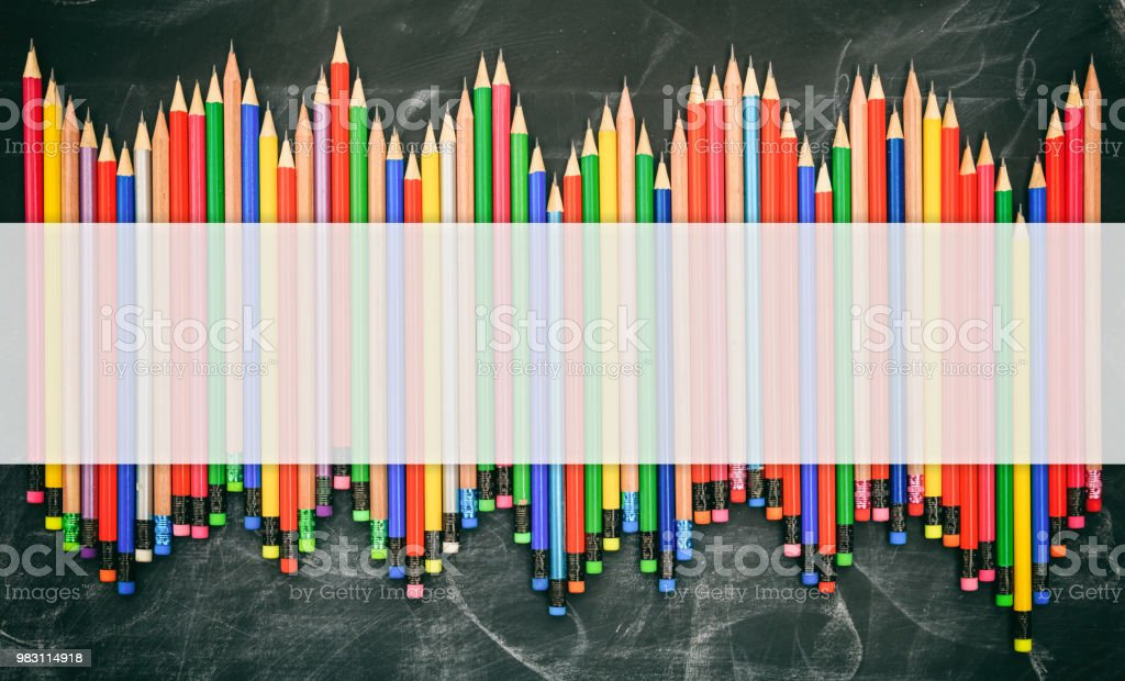 Colored pencils with erasers on a black chalkboard