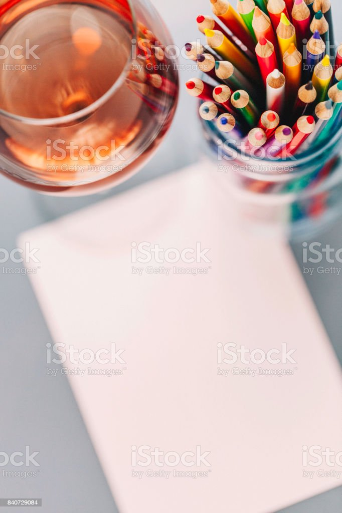 Colored pencils with pink paper and glass of wine stock photo