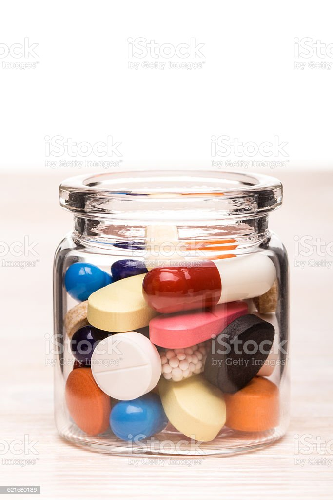 Colored pills in transparent glass container stock photo