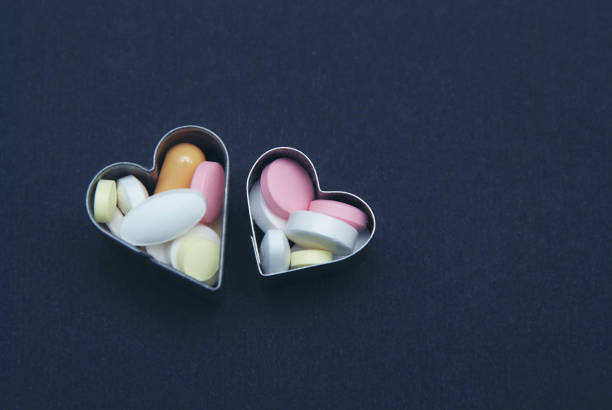 Colored Pills, Tablets and Capsules in Heart Shapes Pharmacy and Medicine, over Dark Background. Healthy and medicine concept. Blue Background. Colored Pills, Tablets and Capsules in Heart Shapes Pharmacy and Medicine, over Dark Background. Blue Background. acetylsalicylic stock pictures, royalty-free photos & images