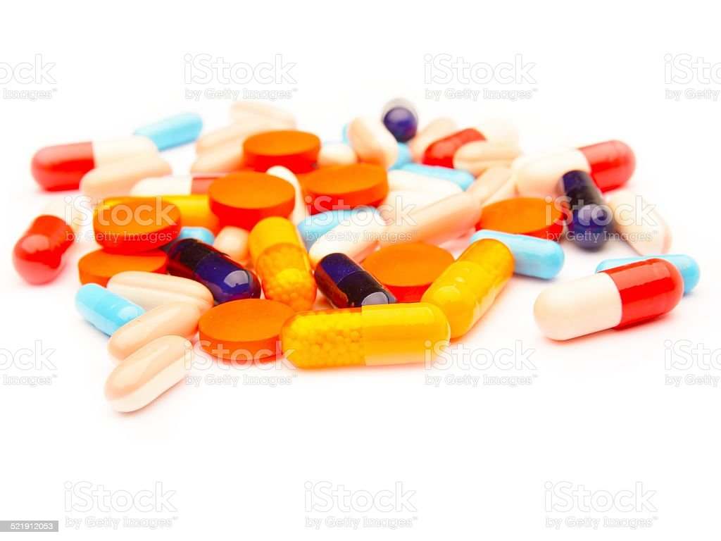 Colored pills, tablets and capsules on a white background stock photo