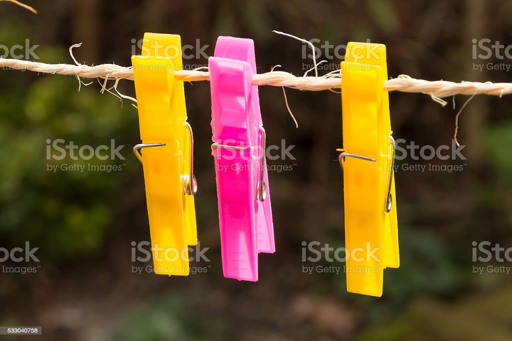 Colored plastic clothes pegs on the clothesline. stock photo