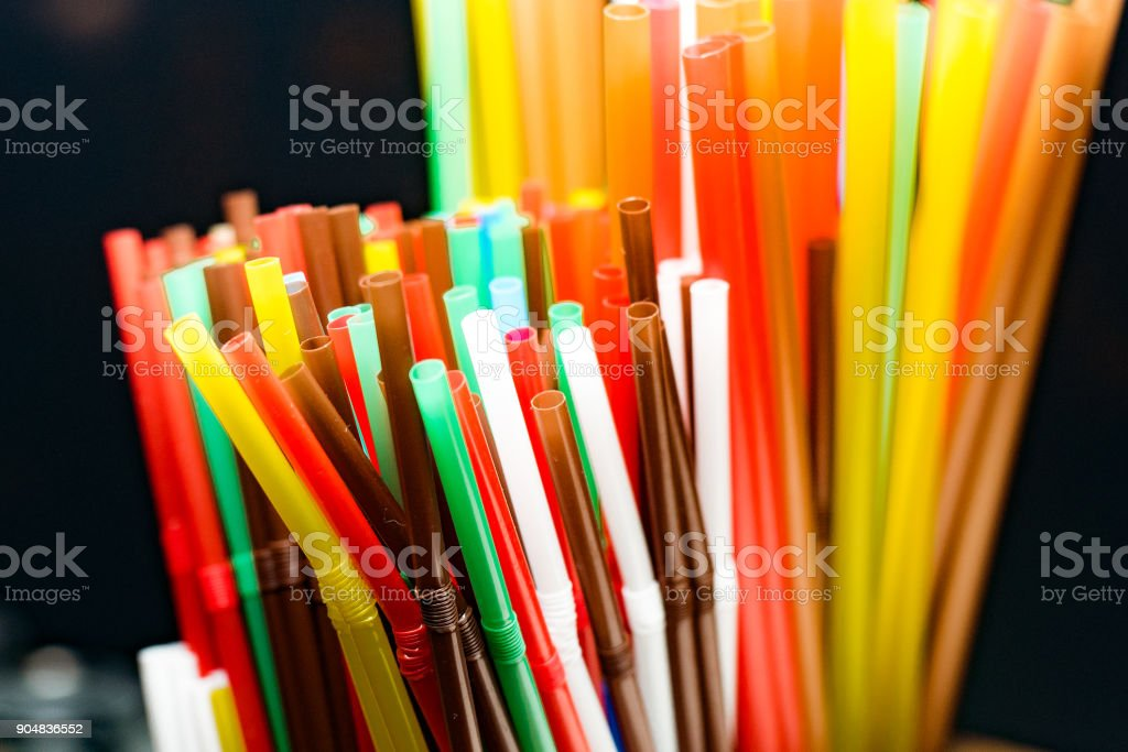 colored plastic cocktail tubes standing in a glass top view, Drinking straws stock photo