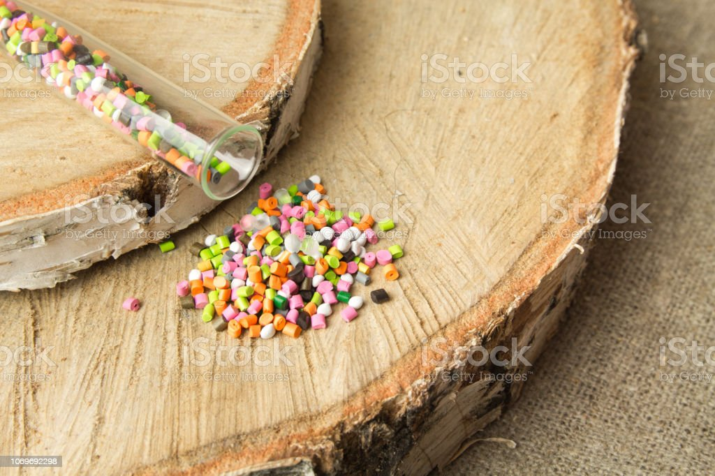 Colored plastic granules  on the background birch.The concept of environmental friendliness of  Polyethylene, polypropylene material. BPA FREE stock photo